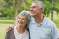 Smiling senior couple with arms around at park women and men the Stock Photos