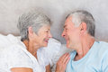 Smiling senior couple in bed looking at each other Royalty Free Stock Images