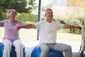 Smiling senior couple exercising together at porch Royalty Free Stock Photo
