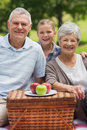 Smiling senior couple and granddaughter with picnic basket at park Stock Photo