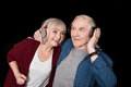 Smiling senior couple listening music in headphones on black Royalty Free Stock Photo