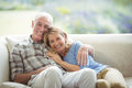 Smiling senior couple sitting together on sofa in living room Royalty Free Stock Photo