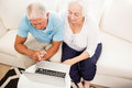 Smiling senior couple using laptop at home Stock Photography