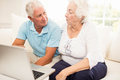 Smiling senior couple using laptop at home Stock Photos