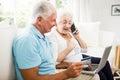 Smiling senior couple using laptop and smartphone Royalty Free Stock Photo