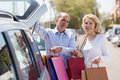 Smiling senior family with bags near car at shopping center parking lot Stock Photo