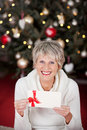 Smiling senior lady with a gift voucher beautiful displayed in her hands sitting in front of decorated christmas tree Stock Photo