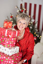 Smiling senior lady with a pile of christmas gifts for her family sitting on the sofa in her living room in front the Royalty Free Stock Photography