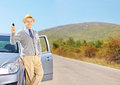 Smiling senior male holding a key next to his automobile car on an open road shot with tilt and shift lens Stock Photos