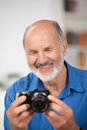 Smiling senior man with a camera bearded in his hands in his living room close up portrait Royalty Free Stock Images