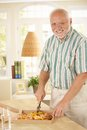 Smiling senior man cutting up pizza with slicer standing by table looking at camera Royalty Free Stock Image