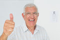 Smiling senior man gesturing thumbs up with eye chart in background portrait of a the at medical office Stock Photo