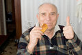 Smiling senior man giving a thumbs up gesture of approval as he munches on fresh roll in his house Royalty Free Stock Photo