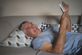 Smiling senior man holding digital tablet while lying on sofa at home Royalty Free Stock Photo