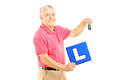 Smiling senior man holding a l plate and car key isolated on white background Royalty Free Stock Images