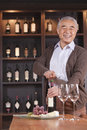 Smiling senior man opening wine bottle and looking at camera shelf with wine in the background men Royalty Free Stock Images