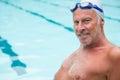 Smiling senior man sitting at poolside Royalty Free Stock Photo