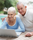 Smiling senior man and woman using a laptop Stock Image
