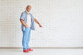Smiling senior is points his finger to the floor Royalty Free Stock Photo