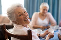 Smiling senior woman playing cards with friends Royalty Free Stock Photo