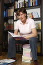 Smiling senior woman sitting on book stack Royalty Free Stock Images