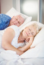 Smiling senior woman sleeping besides husband on bed women in room Royalty Free Stock Photo