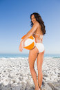 Smiling sexy brunette in white bikini holding beach ball Royalty Free Stock Photo
