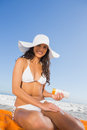 Smiling sexy woman applying sun cream while sitting on her towel the beach Stock Photography