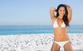 Smiling sexy woman in white bikini posing on the beach Stock Images