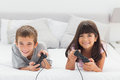 Smiling siblings lying on bed playing video games together at home Royalty Free Stock Photos