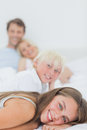 Smiling siblings lying on the bed with their parents behind them Royalty Free Stock Photo