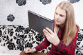 Smiling sitting teen is working on the tablet Royalty Free Stock Images
