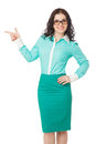Smiling slim brunette girl in green skirt and blouse pointing as beautiful wearing glasses over white background aside Royalty Free Stock Image