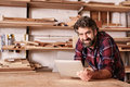 Smiling small business owner in woodwork studio with digital tab portrait of a at the camera resting on his workbench and holding Royalty Free Stock Image