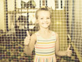 Smiling small girl showing thumbs up on indoor Royalty Free Stock Photo