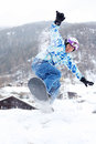 Smiling snowboarder jumps on snowboard on mountain Stock Images