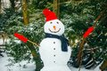 smiling snowman in red hat with gloves Royalty Free Stock Photo