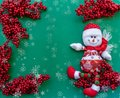 Snowman figurine on red sorb rowan branches green Christmas background Royalty Free Stock Photo