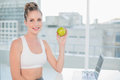 Smiling sporty blonde holding green apple in bright room Royalty Free Stock Image