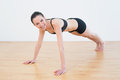 Smiling sporty woman doing push ups in fitness studio beautiful young Royalty Free Stock Photo