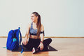 Smiling sporty woman sitting on floor with blue backpack in studio. Fitness and lifestyle concept.