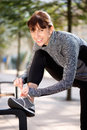 Smiling sporty woman tying shoelace outside portrait of a Stock Images