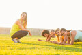 Smiling sporty women planking during fitness class portrait of in parkland Stock Image