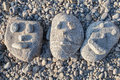 Smiling stones three faces in the beach Stock Photos