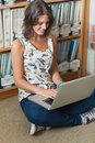Smiling student against bookshelf using laptop on the library floor female sitting and Stock Image