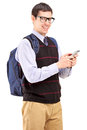 Smiling student with backpack typing a sms on a phone Stock Photography