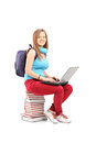 A smiling student with backpack working on a laptop and sitting pile of books white background Stock Images