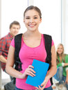 Smiling student with book and school bag Royalty Free Stock Photo