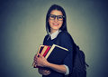 Smiling student carrying a backpack and holding stack of books Royalty Free Stock Photo