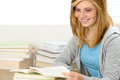 Smiling student girl reading book looking down sitting behind desk Stock Image